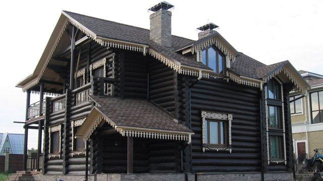 Бревенчатый дом из оцилиндровки с белыми резными наличниками и карнизами