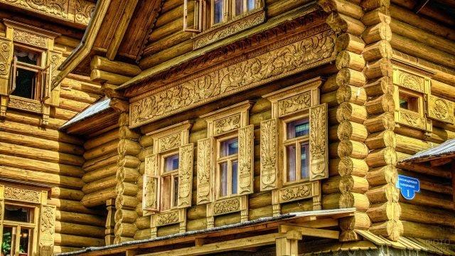 Дом из оцилиндрованного бревна с резным декором фасада в русском стиле