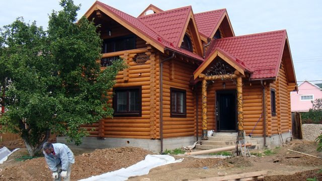 Двухэтажный дом из оцилиндровки с украшением ковкой на крыльце