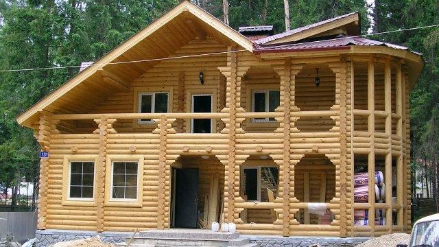 Двухэтажный дом с полукруглой верандой из оцилиндровки на каменном подклёте