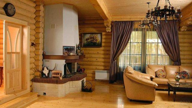 Гостиная с камином в доме из оцилиндровки
