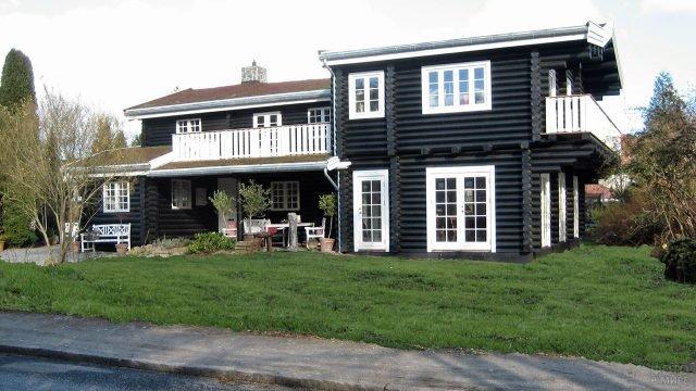 Выкрашенные в чёрный цвет стены эко-дома из оцилиндровки с белыми рамами и балконом