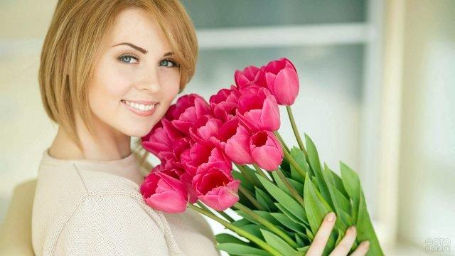 Довольная дама с пышным букетом розовых тюльпанов к 8 марта