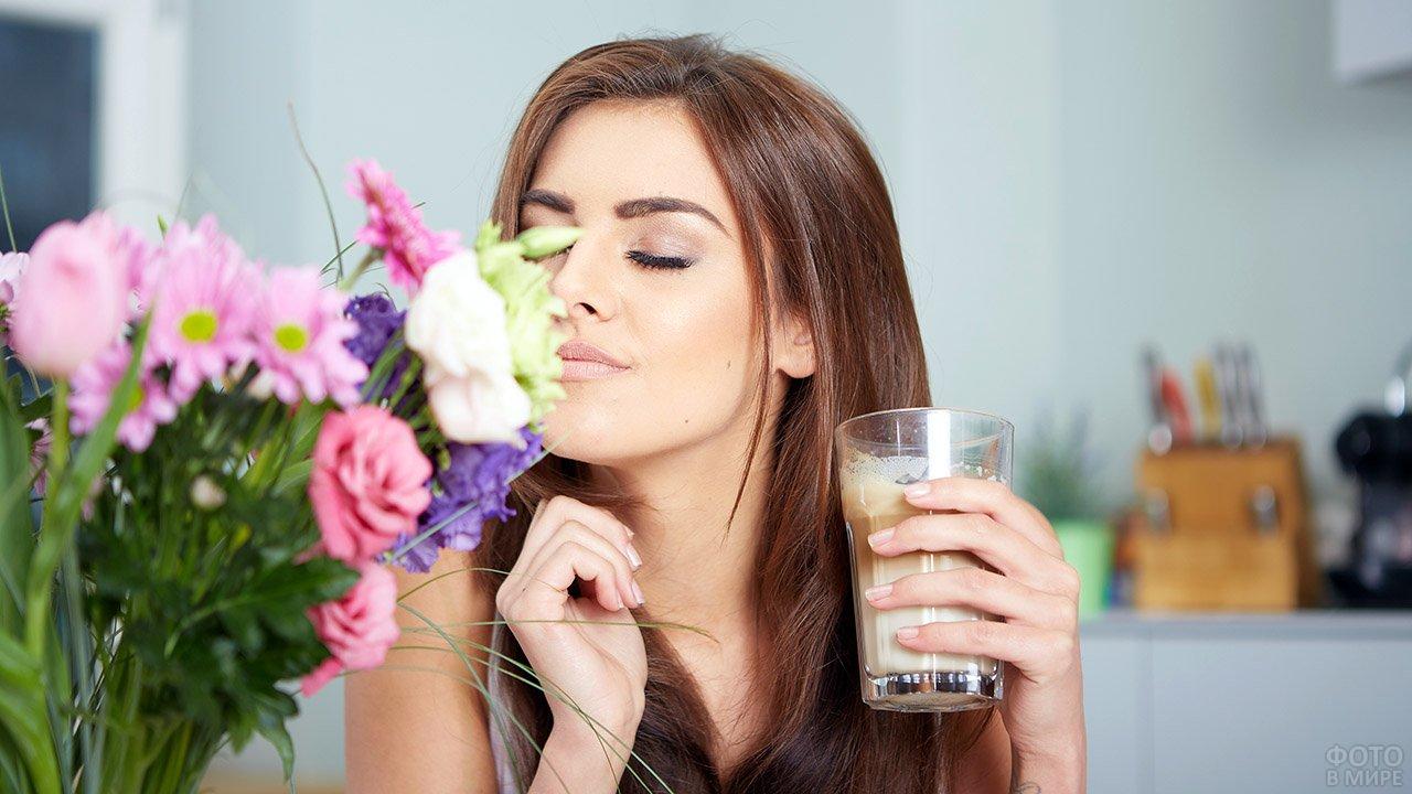 Гламурная девушка со стаканом латте нюхает букет цветов к 8 марта