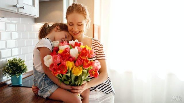 Мама с маленькой дочерью на кухне утром 8 марта с букетом тюльпанов