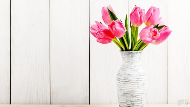Розовые тюльпаны к 8 марта в стильной вазе на белом деревянном фоне