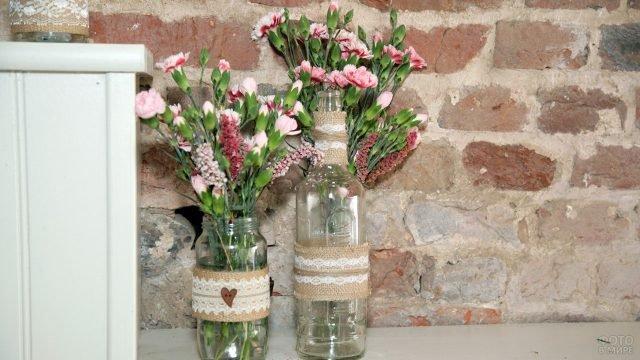 Стильно оформленные кустовые гвоздики к 8 марта на фоне стены в лофт-интерьере