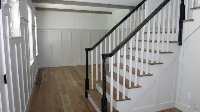 Белое фойе с лестницей с отделкой натуральным деревом