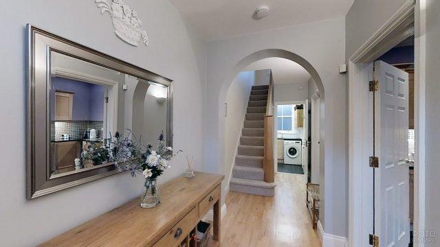 Нежно-лиловый оттенок стен в дизайнерском интерьере прихожей с лестницей