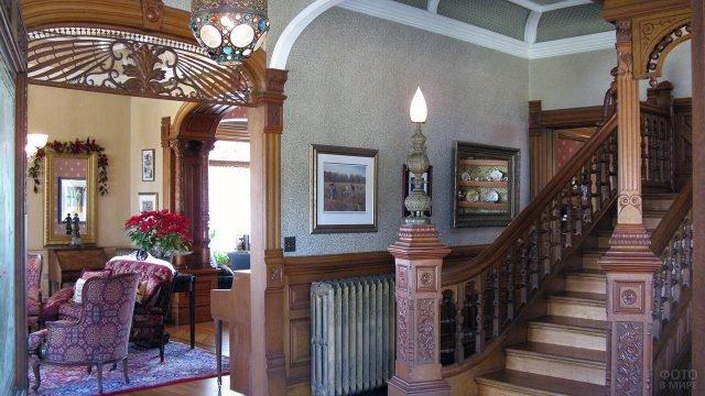 Прихожая в стиле модерн 19 века с резными деревянными панелями и перилами лестницы