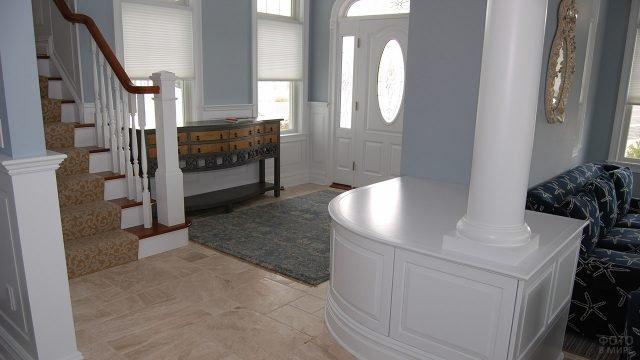 Серое фойе в кабинетном стиле с белыми колоннами и лестницей