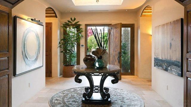 Стол с вазами и круглый ковёр в центре композиции небольшого классического холла