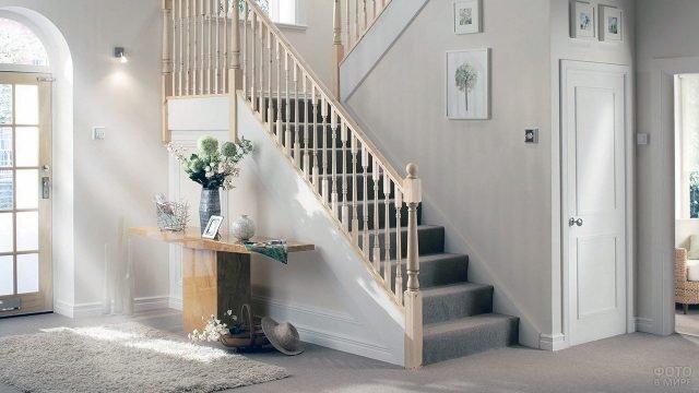 Светлая прихожая с лестницей с деревянными перилами