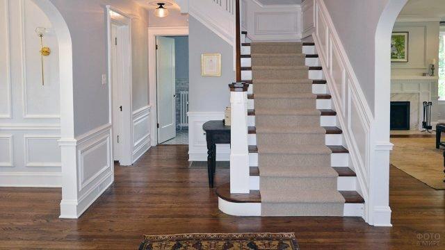 Светло-серая прихожая с лестницей и дубовым паркетом