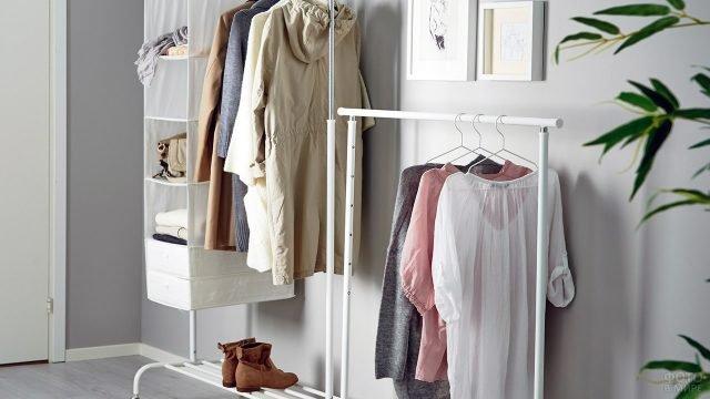 Вешалки с одеждой на фоне светло-серой стены в прихожей