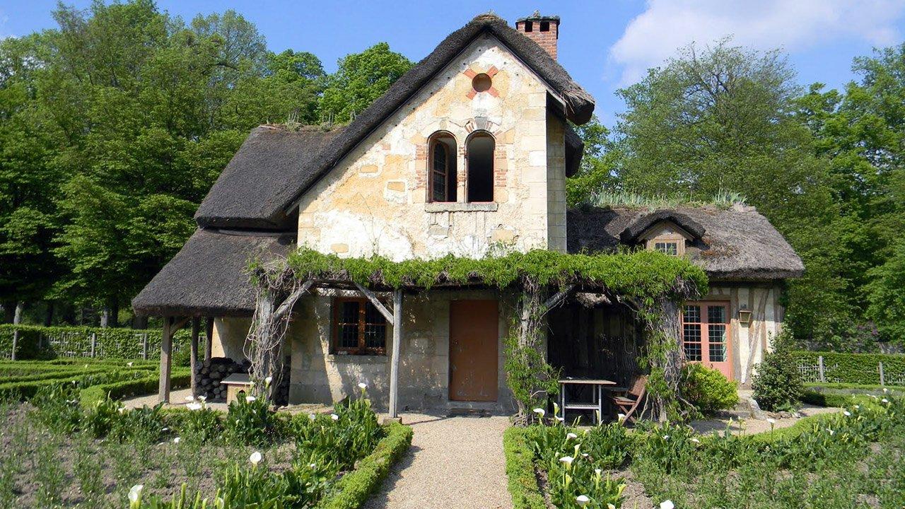 Аутентичный старинный домик с соломенной крышей и зелёной верандой на ферме