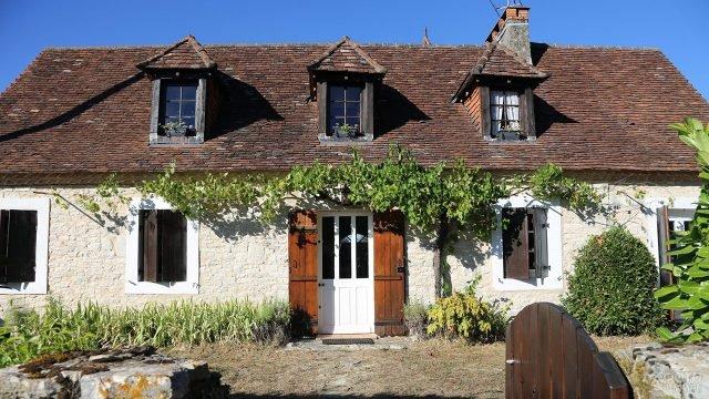 Белый каменый дом с вьюнком на фасаде и мансардным этажом под черепичной крышей