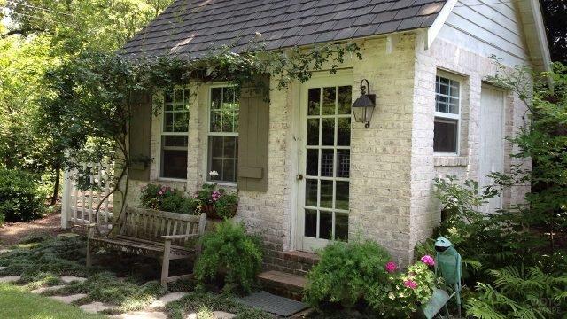 Белый садовый домик из кирпича с деревянными ставнями и черепичной крышей