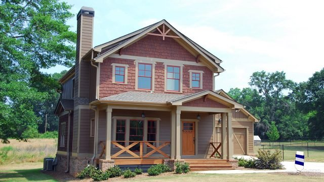 Бежевый двухэтажный дом с открытой верандой и декоративной отделкой фасада