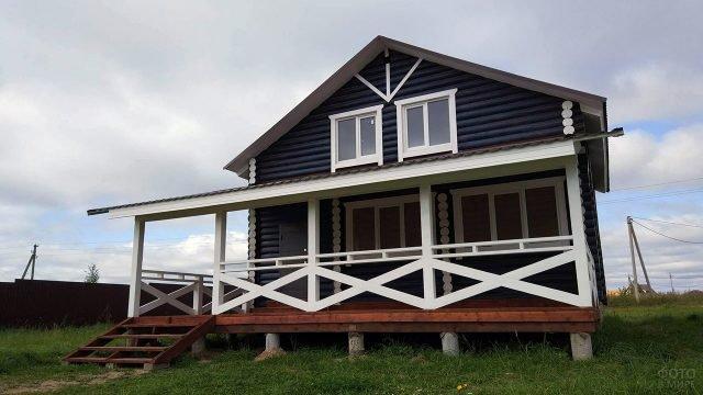 Бревенчатый дом с чёрным фасадом и широким белым крыльцом