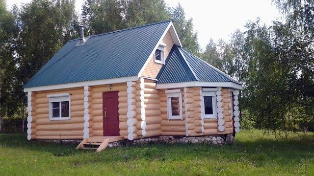 Бревенчатый садовый домик с эркером и зелёной крышей