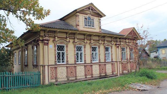 Деревянный русский дом с резным декором фасада