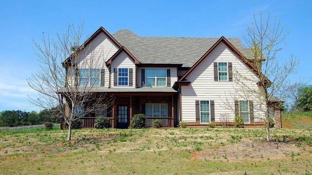 Двухэтажный белый домик с деревянной верандой и зелёной крышей