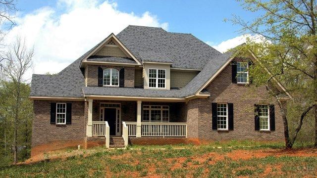 Кирпичный дом с белыми перилами веранды и чёрной черепичной крышей