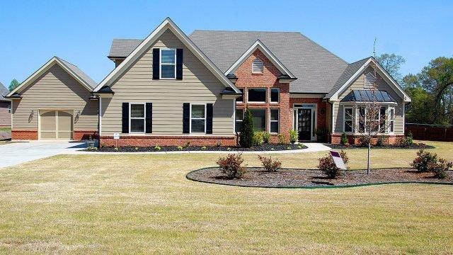 Кирпичный дом с серым сайдингом и чёрными ставнями под чёрной черепичной крышей