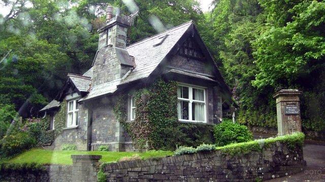 Красивый каменный домик под летним дождём