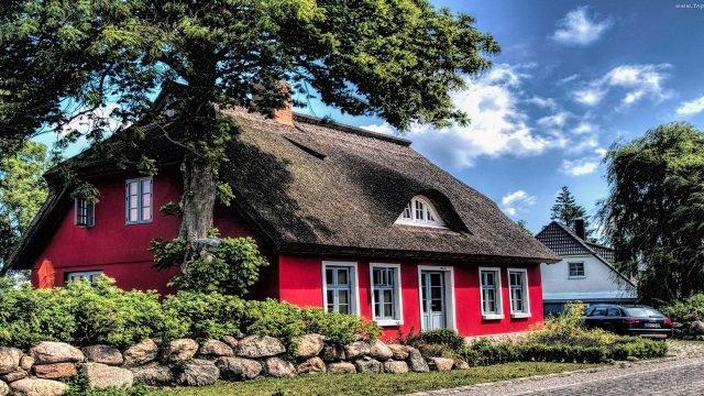 Красный двухэтажный дом с аутентичной сельской крышей под раскидистым деревом