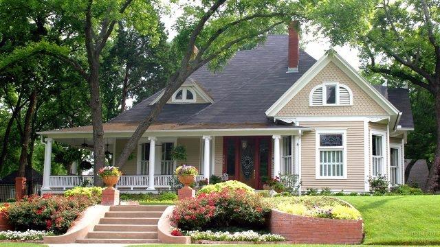 Милый домик с бежевым сайдингом и белыми колоннами на веранде