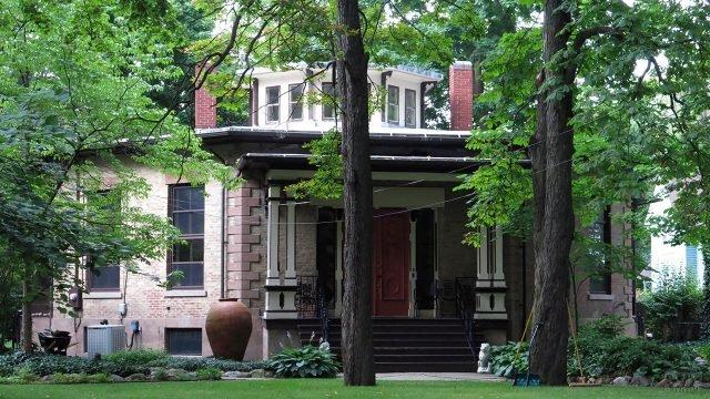 Необычный кирпичный домик с крыльцом в классическом стиле под высокими деревьями