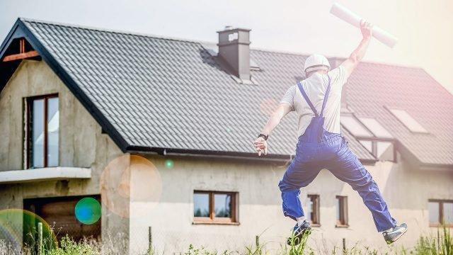 Счастливый строитель на фоне дачного дома с мансардой и крышей из металлочерепицы