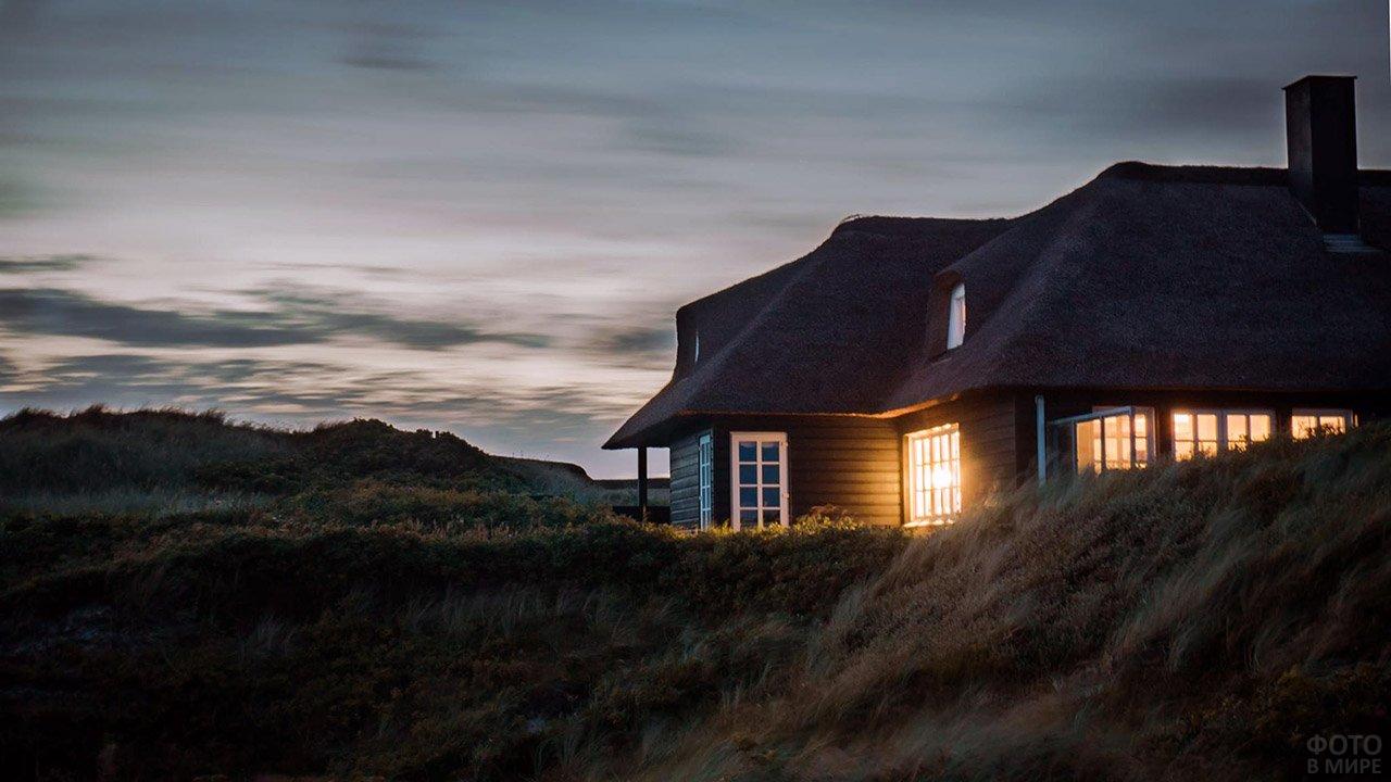 Сельский дом с зажжёнными окнами в вечернем поле