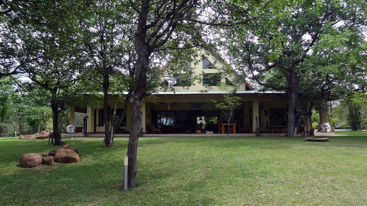 Светло-зелёный дом с просторной верандой под высокими деревьями
