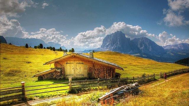 Живописная избушка в жёлтом поле на фоне голубых гор