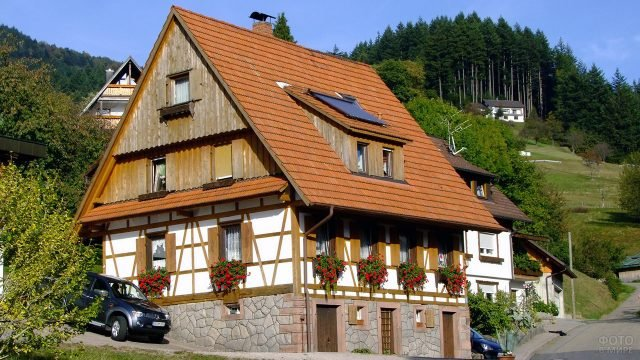 Живописный загородный дом в немецком стиле с черепичной крышей и цветами под окнами