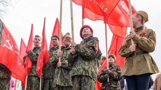 Школьники-волонтёры в военной форме под знамёнами Победы 9 мая
