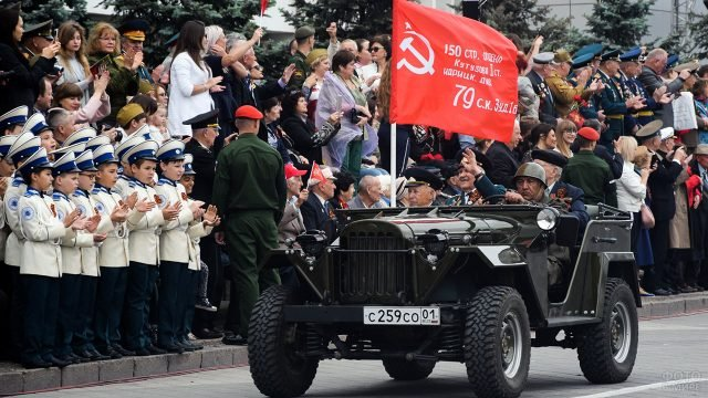 Ветераны со знаменем Победы проезжают в ГАЗ-67 вдоль колонн на параде 9 мая