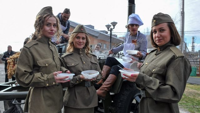 Волонтёры в форме времён ВОВ позируют 9 мая на фоне полевой кухни