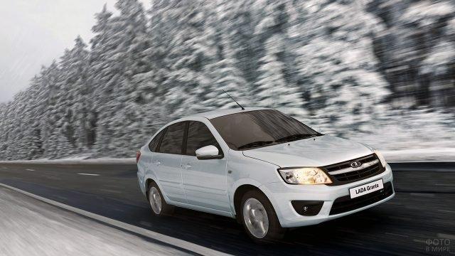 Белая Лада Гранта мчится по трассе на фоне зимнего леса