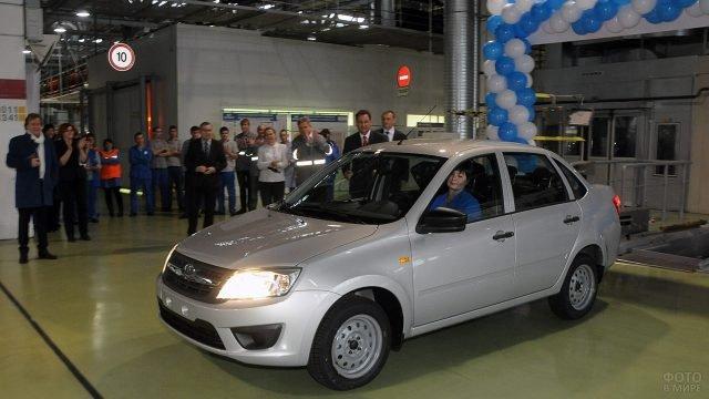 Женщина за рулём выставочной Лады Гранта на презентации в автосалоне продаж