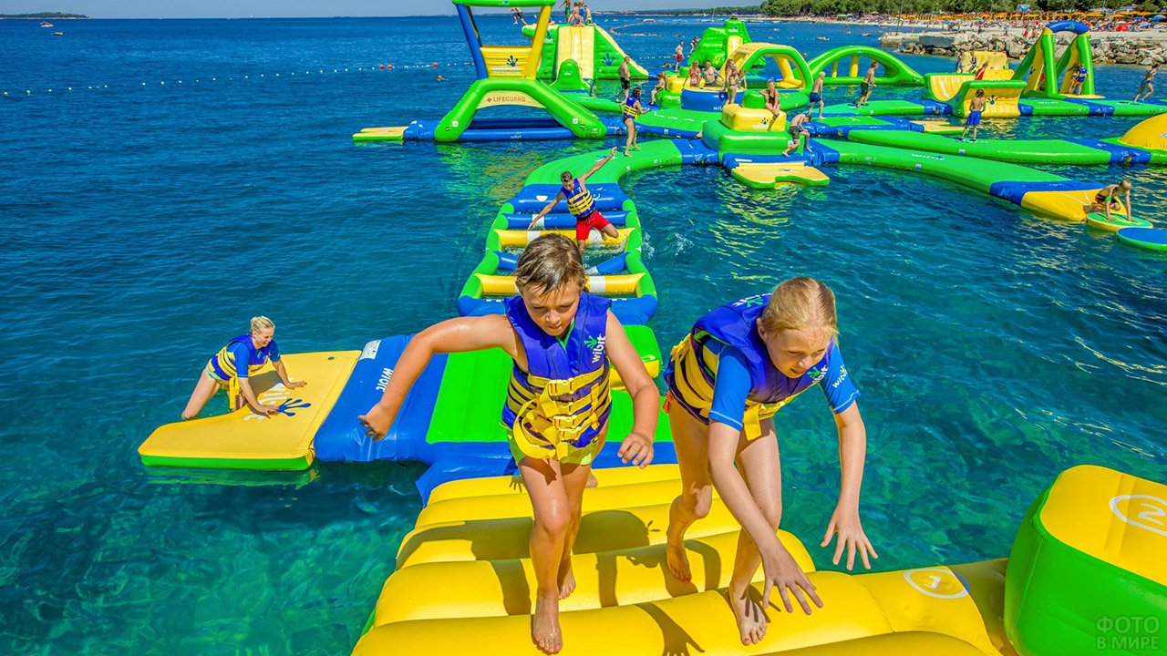 Дети бегут по ступенькам надувного города-квеста на мелководье морского пляжа