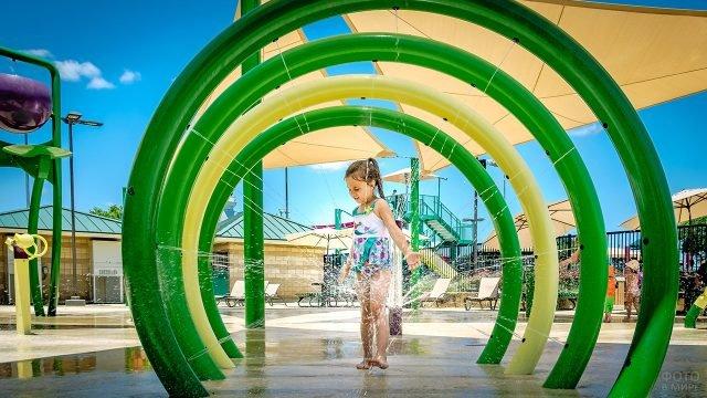 Девочка в фонтане-арке техаского аквапарка