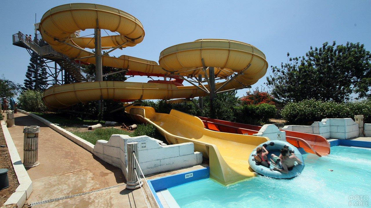 Люди на большом круглом плоту спускаются с водной горки в бассейн аквапарка