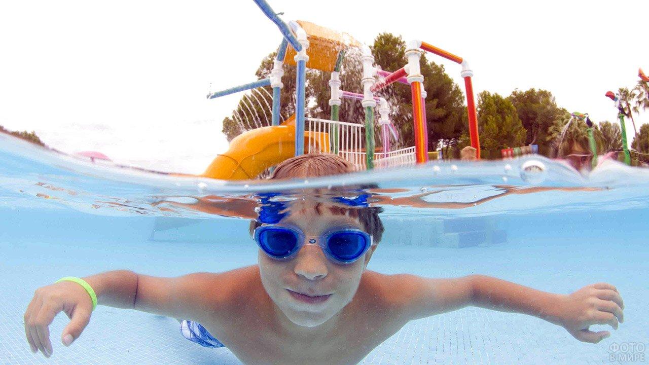 Мальчик под водой в бассейне аквапарка под открытым небом