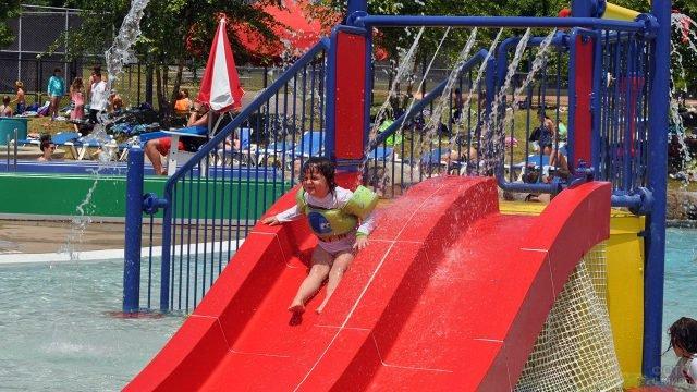 Маленькая девочка на красной аквагорке с фонтаном