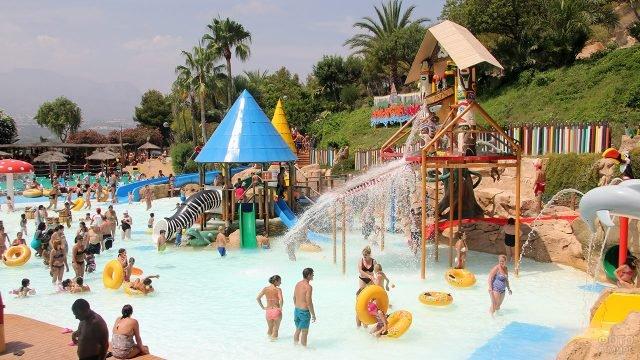 Многолюдный бассейн-лягушатник с детскими горками в испанском аквапарке