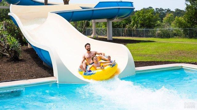 Отец с сыном несутся на жёлтых тюбингах по белой аква-горке